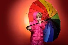 Pys med detfärgade paraplyet som isoleras på röd bakgrund Barnet annonserar din produkt och tjänst gulligt royaltyfria foton