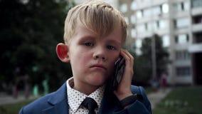Pys med en allvarlig framsida i en affärsdräkt som talar på skottet för telefondockazoom