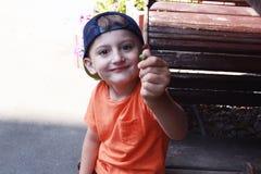 Pys med en ekollon i hans hand nära tabellen på gatan arkivfoto