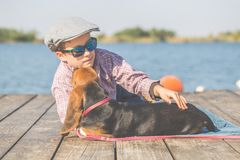 Pys med ett lock som spelar med hans hund vid floden royaltyfria bilder