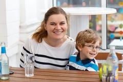 Pys med exponeringsglas och hans moder som tycker om drinkar Royaltyfria Bilder