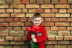 Pys med gruppen av röda tulpan som ser kameran Fotografering för Bildbyråer