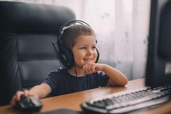 Pys med hörlurar med mikrofon genom att använda datoren arkivbild