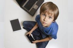 Pys med mobiltelefonsammanträde på golv Digital minnestavla, bärbar dator, dator lite varstans Top beskådar Utbildning Royaltyfri Bild