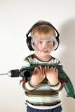 Pys med skyddande exponeringsglas och hörlurar som rymmer drillborren royaltyfri foto