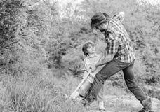 Pys och fader med skyffeln som s?ker efter skatter lycklig barndom Aff?rsf?retagjakt f?r skatter hj?lpreda little royaltyfria bilder