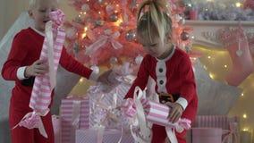 Pys och flicka i Santa Claus dräkter att demontera deras julklappar arkivfilmer