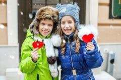 Pys och flicka som rymmer röd hjärta barn två Begreppet av den förälskelse- och för valentin` s dagen royaltyfria bilder