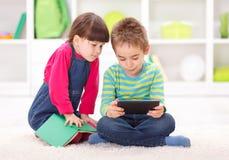 Pys och flicka som spelar eller läser från minnestavlan Arkivfoton