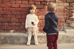 Pys och flicka som spelar med telefonen Royaltyfria Bilder