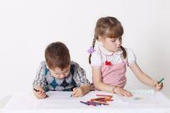 Pys- och flickaattraktion med att sitta för färgpennor royaltyfri foto
