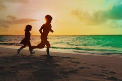Pys- och flickakörningslek på den tropiska stranden för solnedgång arkivfoton