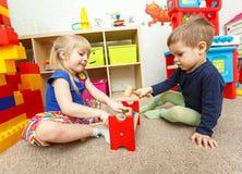 Pys- och flickalek med leksakhammaren i dagis arkivbilder
