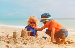 Pys- och flickalek med sand på sommar sätter på land Arkivbild