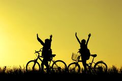 Pys- och flickaridningen cyklar på solnedgången, aktivungesporten, den asiatiska ungen, kontur en unge på solnedgången, lycklig t Arkivfoton