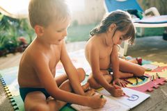 Pys- och flickateckning med färgpennor arkivbild