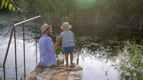 Pys och hans fader på fiske på sjön, familjrekreation under semester stock video