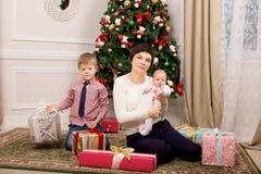 Pys och hans mammasammanträde nära trädet gåvor nytt år arkivfoton
