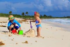 Pys- och litet barnflicka som spelar med sand på Arkivbild