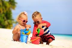 Pys- och litet barnflickan spelar med sand på royaltyfri fotografi