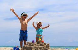 Pys- och litet barnflickan spelar med sand på stranden royaltyfria foton