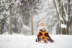 Pys och moder/farmor/barnflicka som glider i parkera under ett snöfall arkivbilder
