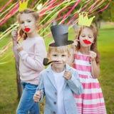 Pys och två flickor som poserar med pappers- maskeringar på gladlynta barns ferie Fotografering för Bildbyråer