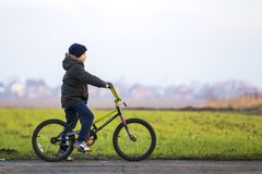 Pys på en cykel utanför barn som leker utomhus Royaltyfria Foton