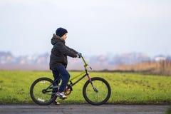 Pys på en cykel utanför barn som leker utomhus Arkivbilder