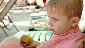 Pys på en vardagsrumstol med en Apple vid pölen lager videofilmer
