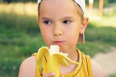 Pys som äter bananen som ser kameran med den lyckliga framsidan som visar upp tummar Den lyckliga ungen tycker om att äta ny fruk Royaltyfria Bilder