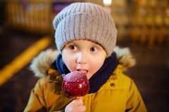 Pys som äter det röda äpplet som täckas i karamell på julmarknad Traditionell child& x27; s-njutning och gyckel under Xmas-tid arkivbild