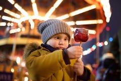 Pys som äter det röda äpplet som täckas i karamell på julmarknad Traditionell child& x27; s-njutning och gyckel under Xmas-tid royaltyfria foton