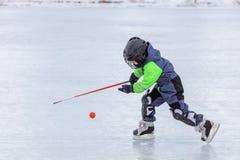 Pys som åker skridskor och spelar hockey Fotografering för Bildbyråer