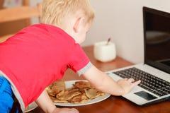Pys som använder bärbar datordatoren som spelar lekar Arkivfoton
