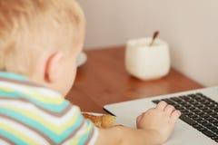 Pys som använder bärbar datordatoren som spelar lekar Arkivbilder