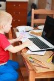 Pys som använder bärbar datordatoren som spelar lekar Royaltyfria Foton