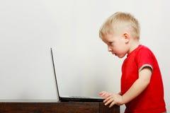 Pys som använder bärbar datordatoren som spelar lekar Royaltyfri Fotografi