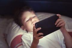Pys som använder minnestavlan på natten i sovrum fotografering för bildbyråer