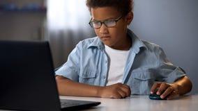 Pys som använder skillfully datormusen för att söka information på internet arkivfoto