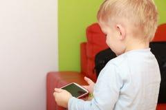 Pys som använder smartphonen som spelar lekar Arkivfoton
