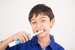 Pys som använder tand- sjukvård för elektriska tandborstar på vit bakgrund Arkivbilder