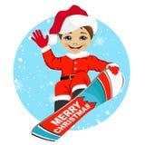 Pys som bär Santa Claus dräktsnowboarding Arkivfoton