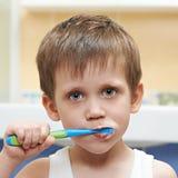 Pys som borstar hans tänder arkivfoto