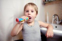 Pys som borstar tänder i bad med den elektriska borsten Royaltyfri Fotografi