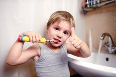 Pys som borstar tänder i bad med den elektriska borsten Arkivfoton