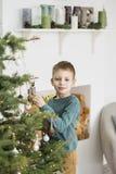 Pys som dekorerar jultr?det med leksaker och bollar Gullig unge som hem f?rbereder sig f?r xmas-ber?m Begreppet av jul royaltyfri bild