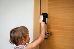 Pys som försöker till öppna dörrar med kortlåset på hotellet royaltyfria bilder