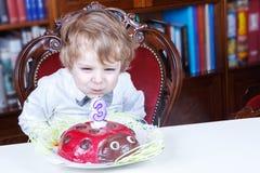 Pys som firar den tredje födelsedagen och blåser av stearinljus Royaltyfri Bild