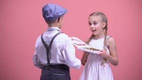 Pys som framlägger chokladgodisar till den förvånade flickvännen, valentindag arkivfilmer